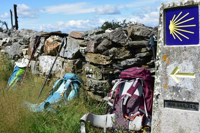 Wanderreise auf dem Jakobsweg Rucksäcke an einer Mauer