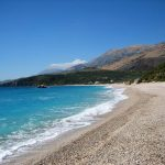 Steinstrand und blaues Meer
